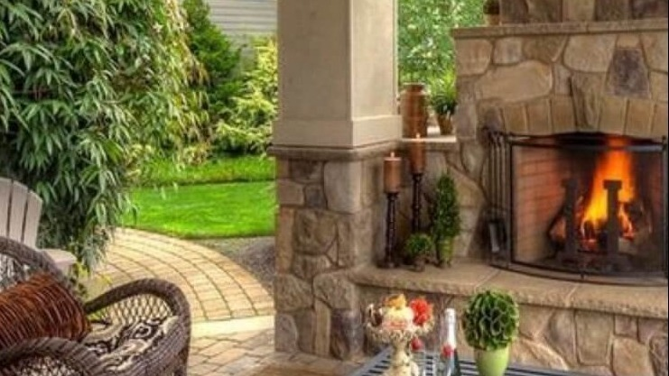 outdoor living construction featuring a fireplace and brick hearth
