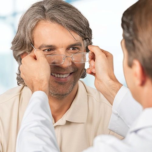 an eye exam patient with doctor trying on glasses