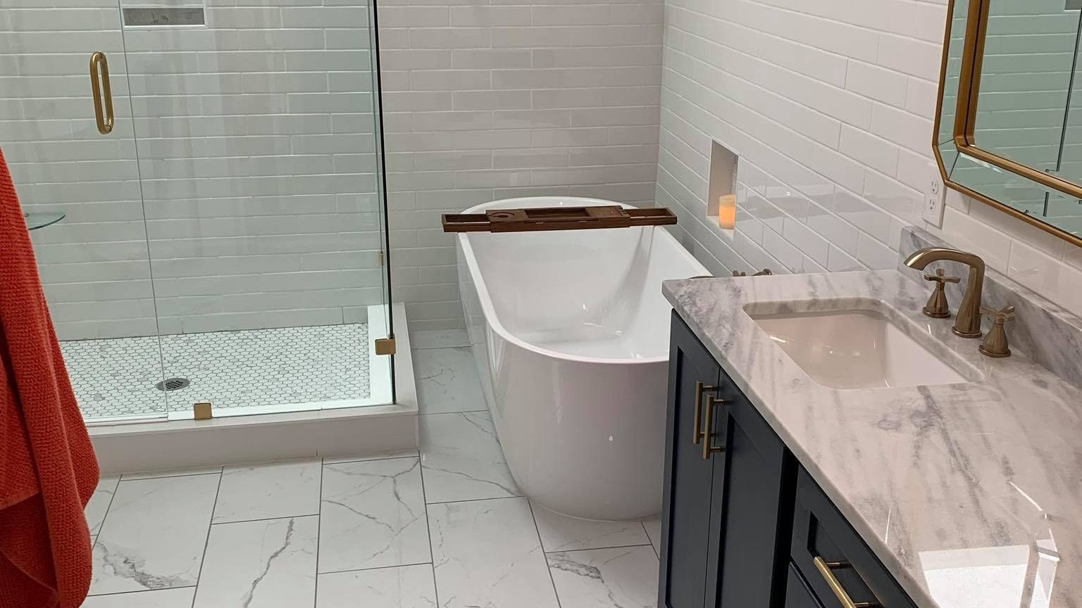 bathroom renovations with tub and glass shower and brown vanity cabinets with mirror