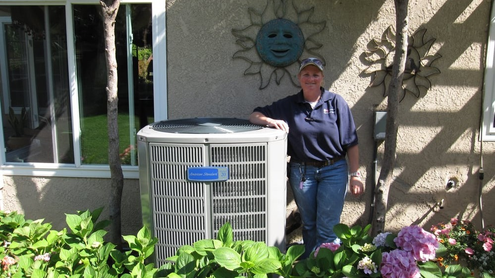 Kelly Mae standing next to an AC unit