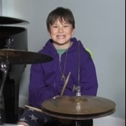 Young boy in front of drum set